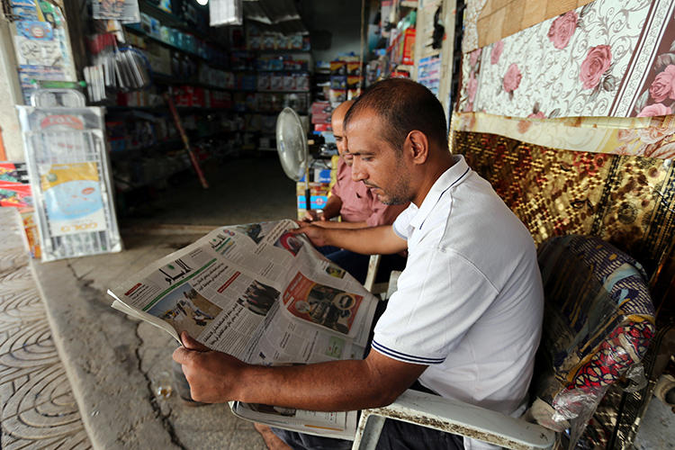 A Palestinian man reads a newspaper outside his store in Gaza City. The executive director of the Palestinian Journalists' Syndicate was recently detained and beaten by security forces in Gaza.