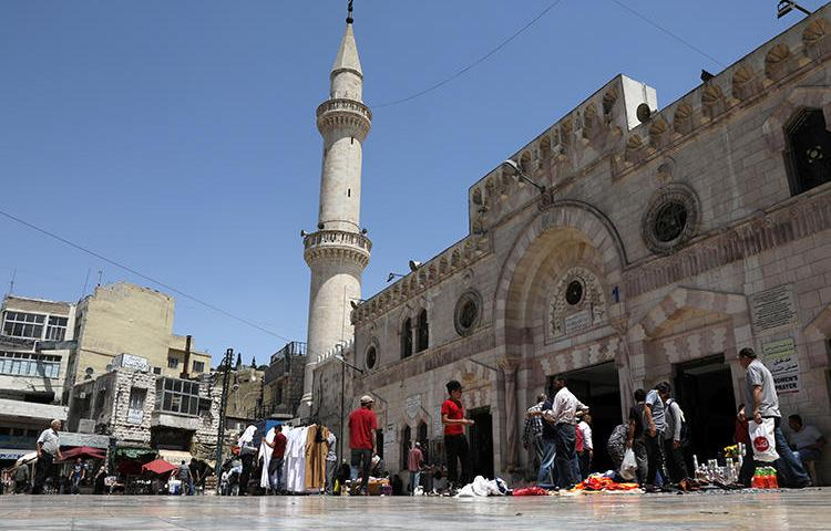 People walk past street vendors outside a mosque in Amman, Jordan, on June 6, 2018. A journalist was imprisoned over an article on a private hospital on January 2, 2019. (Reuters/Ammar Awad)