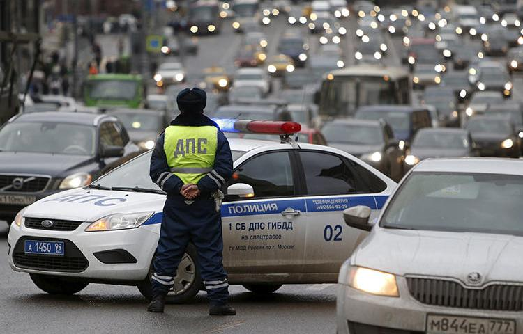 A Russian traffic police officer stands guard as vehicles drive past in central Moscow. In Far Eastern Russia, a blogger was recently detained by authorities, ostensibly for a traffic violation. He maintains that the arrest is linked to a video he shared online. (Sergei Karpukhin/Reuters)