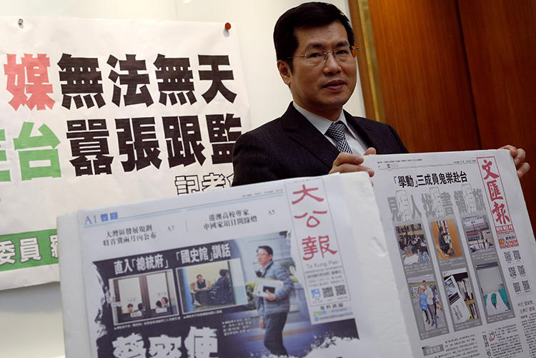Democratic Progressive Party lawmaker Lo Chih Cheng poses with copies of Hong Kong's Ta Kung Pao and Wen Wei Po newspapers after a news conference, in Taipei, Taiwan, on January 18, 2019. (Tyrone Siu/Reuters)