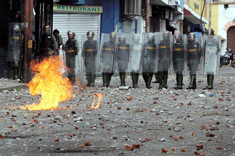 Fuerzas de seguridad observan durante choques en una manifestación en Venezuela el 24 de enero. En medio de la crisis política y manifestaciones en todo el país, las autoridades Venezolanas han allanado medios, detenido a periodistas y confiscado equipos. (Reuters/Carlos Eduardo Ramirez)