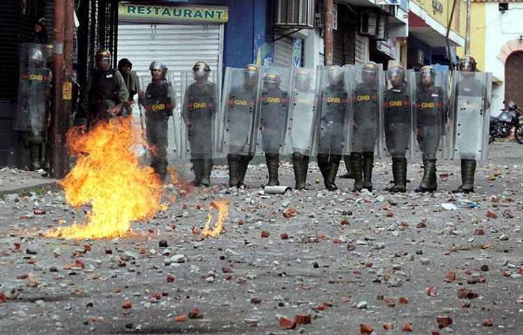Forças de segurança observam os confrontos durante manifestação na Venezuela em 24 de janeiro. Em meio à crise política e aos protestos generalizados, as autoridades venezuelanas invadiram meios de comunicação, prenderam jornalistas e confiscaram equipamentos. (Reuters / Carlos Eduardo Ramirez)