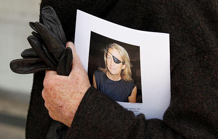 A man holds a sign honoring Sunday Times journalist Marie Colvin after a memorial service in London in 2012. A U.S. court ruled on January 30, 2019, that the Syrian government deliberately killed her. (Reuters/Stefan Wermuth)