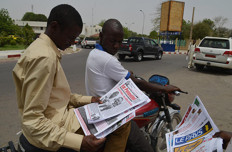 A man reads a newspaper in street in N'djamena, Chad, on April 12, 2016. A publisher was recently handed a suspended jail term in a defamation suit involving the president's brother. (Issouf Sanogo/AFP)