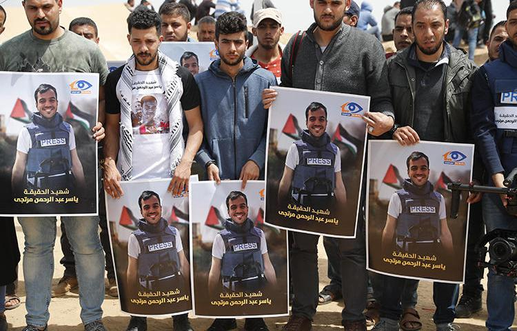 Palestinians hold portraits of reporter Yasser Murtaja on April 13, 2018. A UN commission recently stated that Murtaja and fellow Palestinian journalist Ahmed Abu Hussein were 'intentionally shot' by Israeli snipers. (Thomas Coex/AFP)