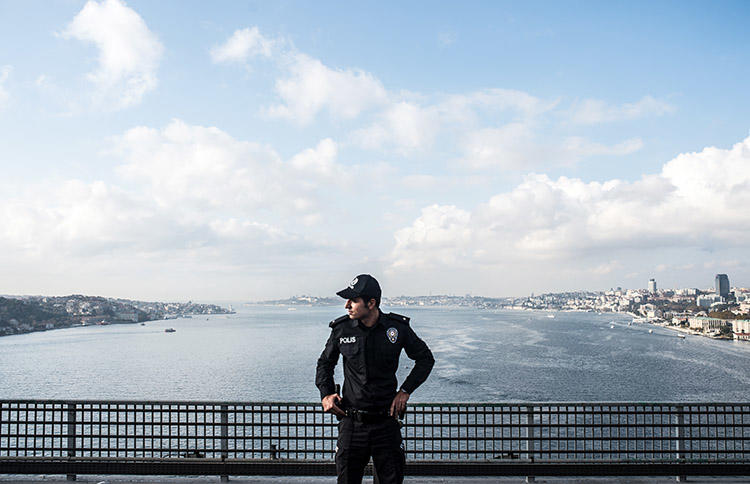 A police officer stands guard on a bridge during the 2018 Istanbul marathon. Two journalists were detained after separate raids in the city in February 2019. (AFP/Bulent Kilic)