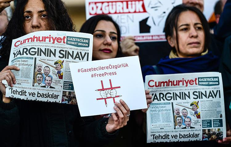Protesters hold copies of Turkish daily newspaper Cumhuriyet during a demonstration in front of a courthouse in Istanbul on October 31, 2017. Today, the Istanbul appeals court rejected several appeals relating to the Cumhuriyet case. (Yasin Akgul/AFP)