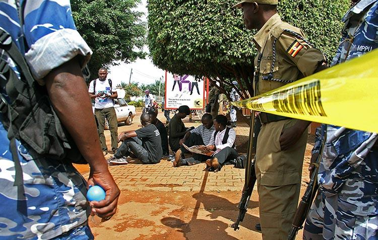 Ugandan journalists sit outside the office of the Daily Monitor, which was closed on May 20, 2013, by armed police. The Monitor's website was recently ordered to suspend publication over a regulatory dispute. (Isaac Kasamani/AFP)
