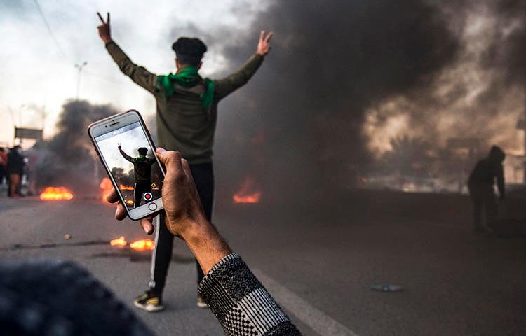 A protester uses his cell phone to film at a demonstration in Basra in January. Militias and Iraqi security forces are attacking and detaining journalists who cover protests in the city. (AFP/Hussein Faleh)