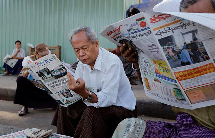 People read local newspapers in Yangon, Myanmar, on January 30, 2017. Two journalists working in Kachin stat were recently detained and assaulted by a local mining company there. (Thein Zaw/AP)
