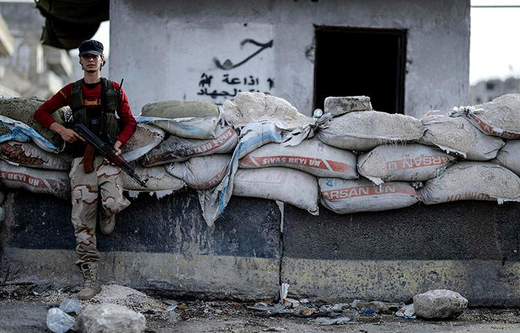 A Syrian opposition fighter stands at a checkpoint in Idlib province on October 13, 2018. A journalist was recently injured in Idlib while covering a government shelling campaign there. (Ugur Can/DHA via AP)