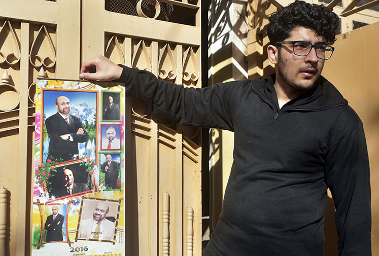 Osama Rizi, son of journalist Rizwan-ur-Rehman Razi, displays a calendar with pictures of his father outside his residence in Lahore, Pakistan, Saturday, Feb. 9, 2019. Pakistani authorities detained Razi, who allegedly criticized state agencies on traditional and social media, officials said Saturday. (AP/K.M. Chaudary)