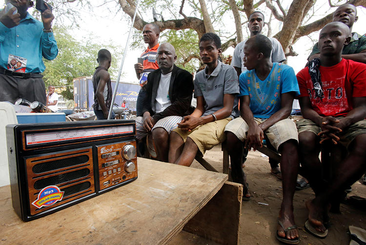 People listen to a radio in Monrovia, Liberia, on December 27, 2017. The Roots FM radio station in Monrovia was recently attacked in two separate incidents. (Thierry Gouegnon/Reuters)