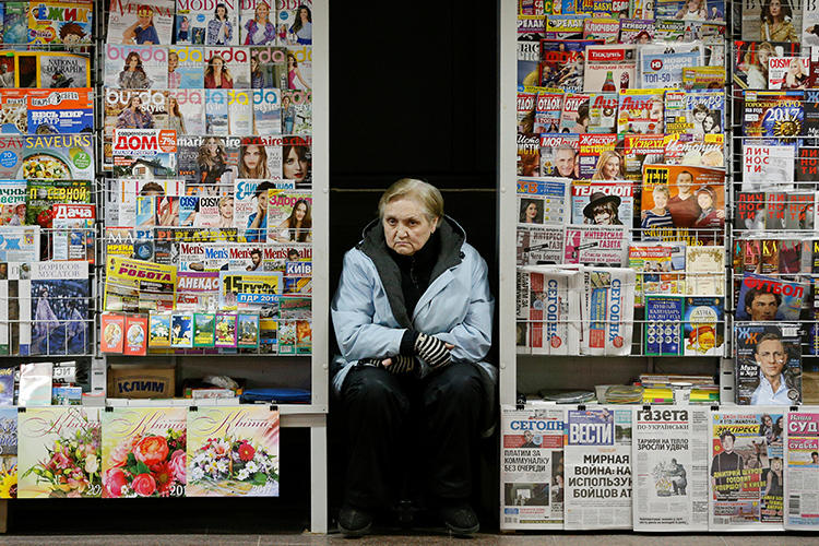 A vendor of magazines, newspapers, and calendars sits in an underground walkway in central Kiev, Ukraine, on November 18, 2016. A Ukrainian court granted the prosecutor general access to a news magazine's files and reporter's emails in February 2019. (Reuters/Valentyn Ogirenko)
