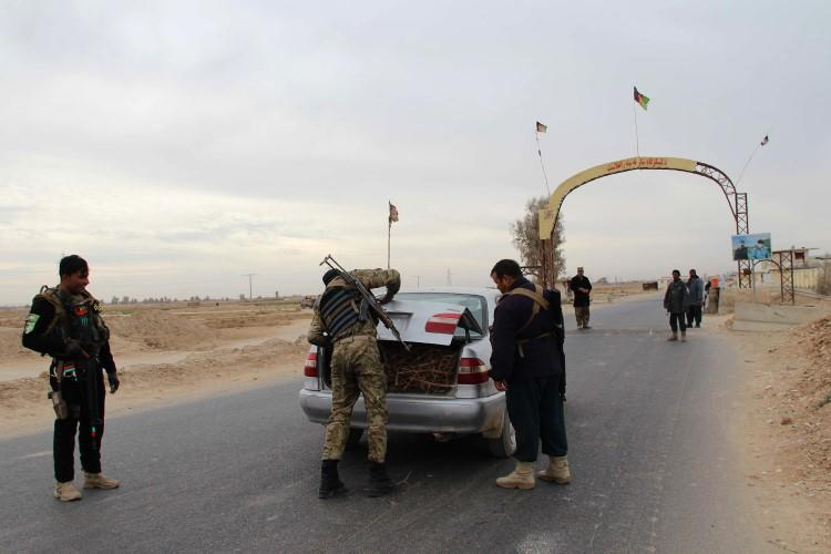 Afghan policemen search passengers at a checkpoint in Helmand province on December 17, 2017. A journalist in Helmand was recently injured by a car bomb in an assassination attempt. (Noor Mohammad/AFP)