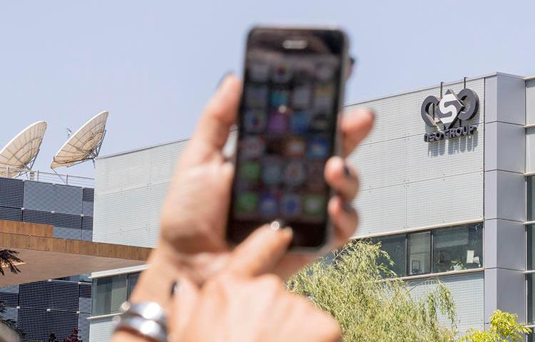 A woman uses her iPhone in front of the building housing NSO Group on August 28, 2016, in Herzliya, near Tel Aviv, Israel. The company has come under increased scrutiny for the alleged use of its spyware tool, Pegasus, to target journalists. (AFP/Jack Guez)