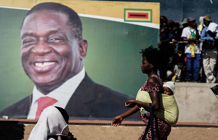 A woman walks in front of a picture of President Emmerson Mnangagwa in Bulawayo, in June 2018. Authorities in the Zimbabwean city detained documentary filmmaker Zenzele Ndebele on March 21. (AFP/Zinyange Auntony)