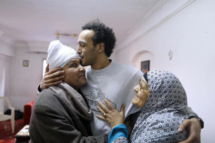 Egyptian photojournalist Mahmoud Abou Zeid, also known as Shawkan, center, is hugged by his parents at his home in Cairo, Egypt, Monday, March 4, 2019. Shawkan was released after five years in prison. (AP Photo/Amr Nabil)