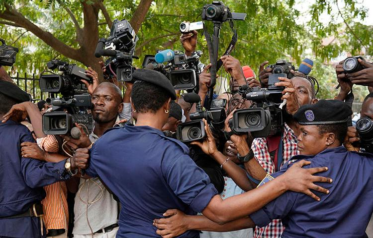Congolese police officers hold back members of the media in Kinshasa, Democratic Republic of Congo, on January 12, 2019. Journalist Steeve Mwanyo Iwewe was recently fined and sentenced to one year in jail for insulting the governor of Équateur province. (Jerome Delay/AP)