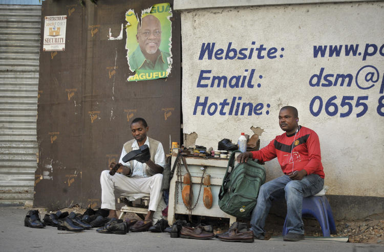 A Tanzanian shoe-shiner conducts his business underneath an election poster for then ruling party presidential candidate, and later president, John Magufuli, in Dar es Salaam, Tanzania, on October 27, 2015. On March 28, 2019, the East African Court of Justice found that multiple sections of Tanzania's Media Services Act restrict press freedom. (AP Photo/Khalfan Said)