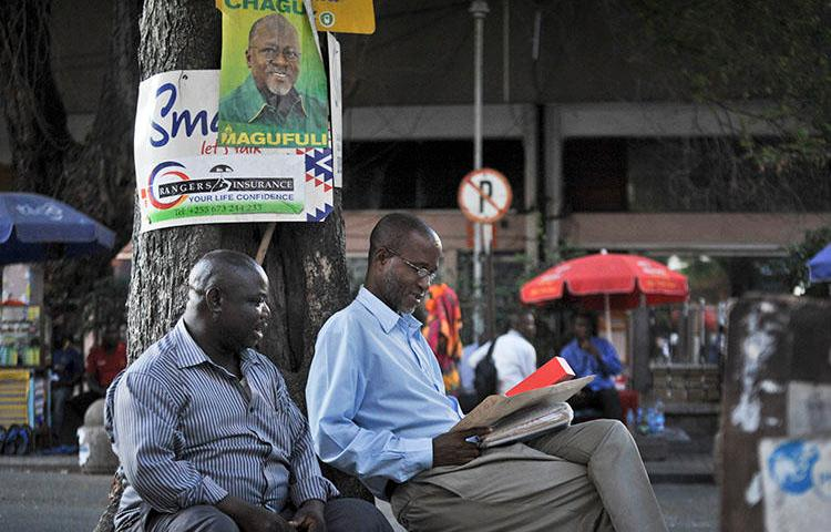 Tanzanians sit next to a tree in Dar es Salaam in 2015. Tanzanian authorities this week imposed a temporary ban on The Citizen over its reporting. (AP/Khalfan Said)