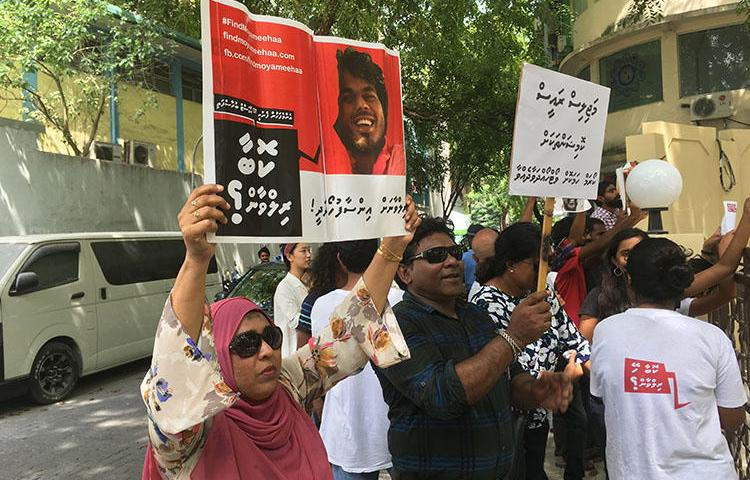 Fathimath Shehenaz holds a sign outside the Malé parliament in February, calling for justice for her brother, the blogger Ahmed Rilwan, who was abducted in 2014. (CPJ)
