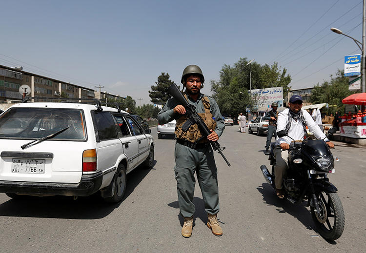 An Afghan police officer inspects vehicles at a checkpoint in Kabul on August 6, 2017. An Afghan journalist was recently killed when he was shot by two unidentified men in Khost. (Mohammad Ismail/Reuters)