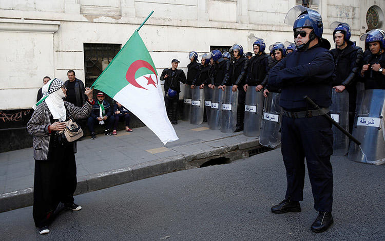 A woman carries a flag in front of police during a protest in Algiers on March 29. Amid weeks of unrest, Algerian journalists are staging their own demonstrations over censorship. (Reuters/Ramzi Boudina)