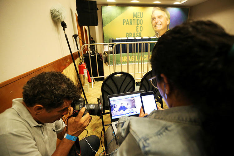Journalists follow a Facebook Live of Jair Bolsonaro, far-right lawmaker and presidential candidate of the Social Liberal Party (PSL), in Rio de Janeiro, Brazil, October 7, 2018. After taking office in January, Bolsonaro and his supporters have made Brazilian journalists' jobs more difficult. (Reuters/Sergio Moraes)