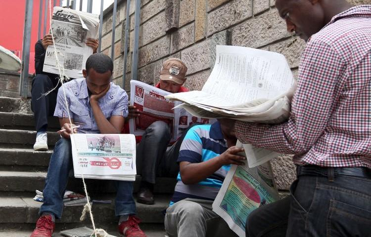 People read newspapers in Ethiopia's capital, Addis Ababa, on May 22, 2015. Two journalists were recently detained and attacked while reporting in Legetafo, a town in Ethiopia's Oromia region. (Tiksa Negeri/Reuters)
