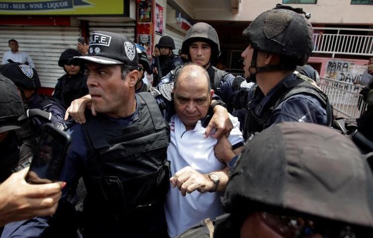 Policías arrestan al periodista David Romero en Tegucigalpa, Honduras, el 28 de marzo de 2019. La Corte Suprema sentenció en enero que el director de Radio Globo y Globo TV debe cumplir una de condena de 10 años por difamación. (Reuters/Jorge Cabrera)