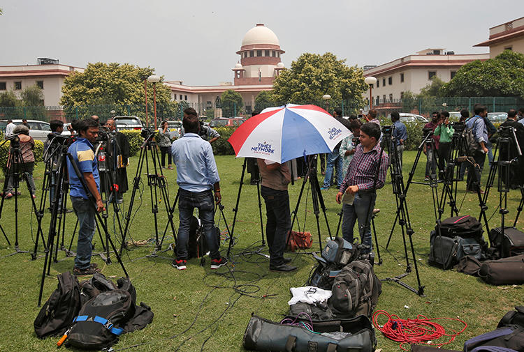 Television journalists are seen outside the premises of the Supreme Court in New Delhi, India, August 22, 2017. The Indian government threatened to invoke Official Secrets Act against two news outlets on March 6, 2019. (Reuters/Adnan Abidi)