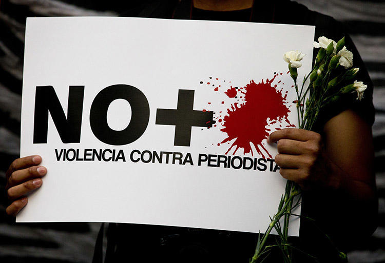 """No more violence against journalists,"""" reads a sign held by a protester during a demonstration outside the Interior Ministry in Mexico City on May 16, 2017. (AP/Rebecca Blackwell)"""