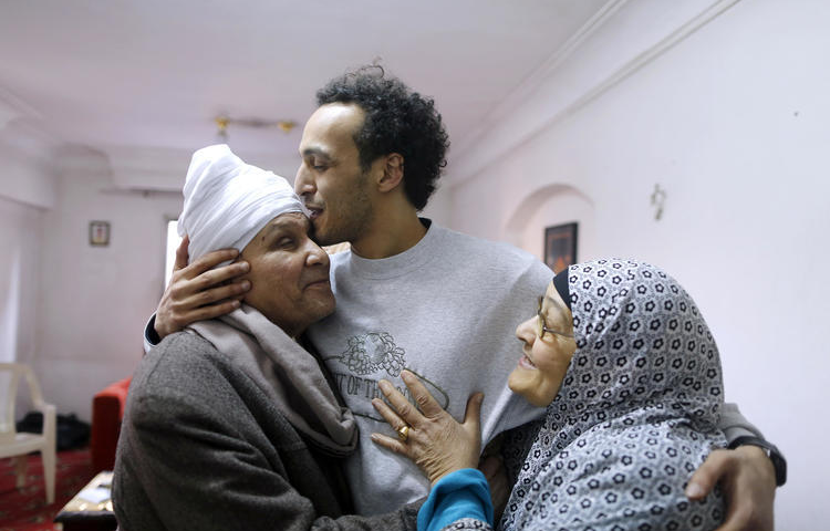 Egyptian photojournalist Mahmoud Abou Zeid, known as Shawkan, is hugged by his parents at his home in Cairo, Egypt, on March 4, 2019. (Amr Nabil/AP)