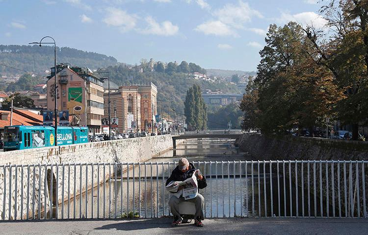 A man reads on a bridge in Sarajevo, Bosnia and Herzegovina, on October 6, 2018. A Sarajevo politician recently attacked a journalist in the city. (Amel Emric/AP)