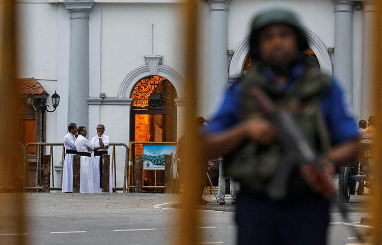 Priests are seen in the background as security personnel stand guard in front of St Anthony's shrine on April 29, 2019, days after a string of suicide bomb attacks across the island on Easter Sunday killed hundreds. (Reuters/Danish Siddiqui)
