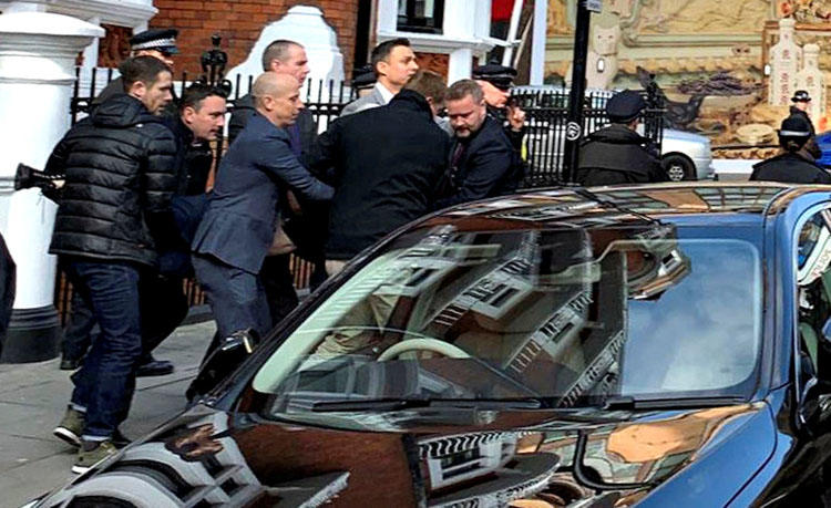 Metropolitan Police officers carry WikiLeaks founder Julian Assange during his arrest, following the Ecuadoran government's termination of asylum, in London on April 11, 2019. (Adrian Cotterill/Daily Dooh via Reuters)