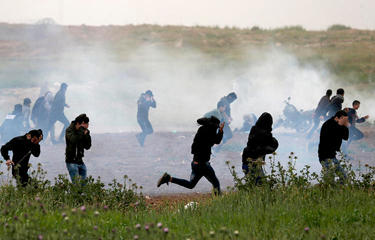 Palestinian protesters run for cover as Israeli forces fire tear gas canisters east of Gaza City on March 30, 2019. At least 10 journalists have been hurt by Israeli forces since late March. (AFP/Mahmud Hams)