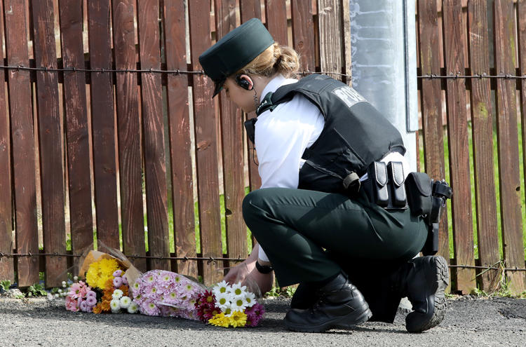 A police officer lays flowers passed to her by members of the public at the scene where journalist Lyra McKee was fatally shot amid rioting overnight in the Creggan area of Londonderry in Northern Ireland on April 19, 2019. (AFP/Paul Faith)