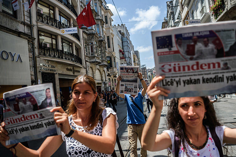 Protesters hold up copies of the pro-Kurdish daily Özgür Gündem during a rally in Istanbul in June 2016. Turkish courts will proceed with 14 cases against a former publisher of the now shuttered newspaper. (AFP/Oan Kose)