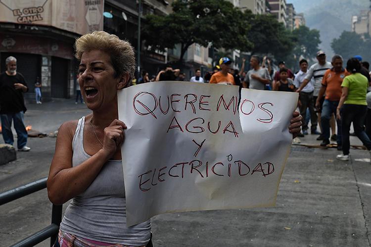 Una mujer sostiene una pancarta que dice 'Queremos Agua y Electricidad' durante una protesta durante el corte de electricidad en Venezuela, en la Avenida Fuerzas Armadas en Caracas el 31 de marzo de 2019. La policía venezolana detuvo al reportero Danilo Gil mientras cubría protestas el 30 de marzo en Ciudad Ojeda, y lo imputaron por resistencia a la autoridad. (AFP/Federico Parra)