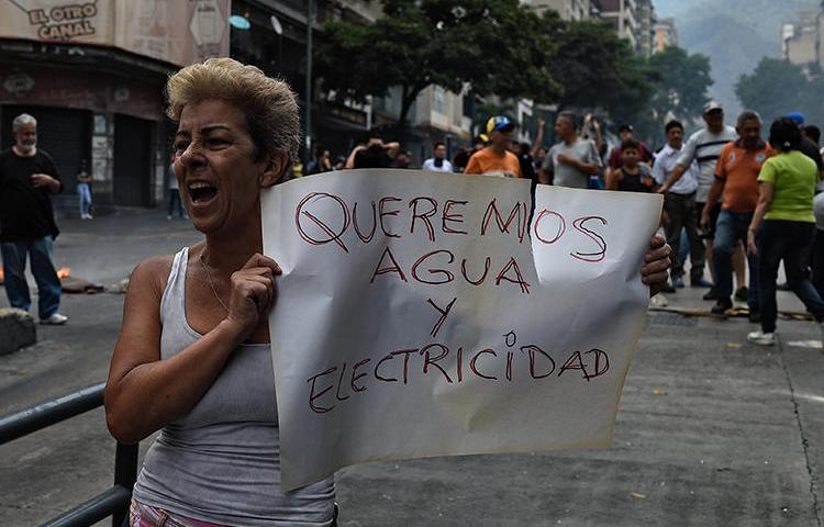 "A woman holds a placard reading ""We Want Water and Electricity"" during a protest during a new power outage in Venezuela, at Fuerzas Armadas Avenue in Caracas on March 31, 2019. Venezuelan police detained reporter Danilo Gil while covering protests on March 30 in the town of Ciudad Ojeda, and charged him with resisting authority. (AFP/Federico Parra)"