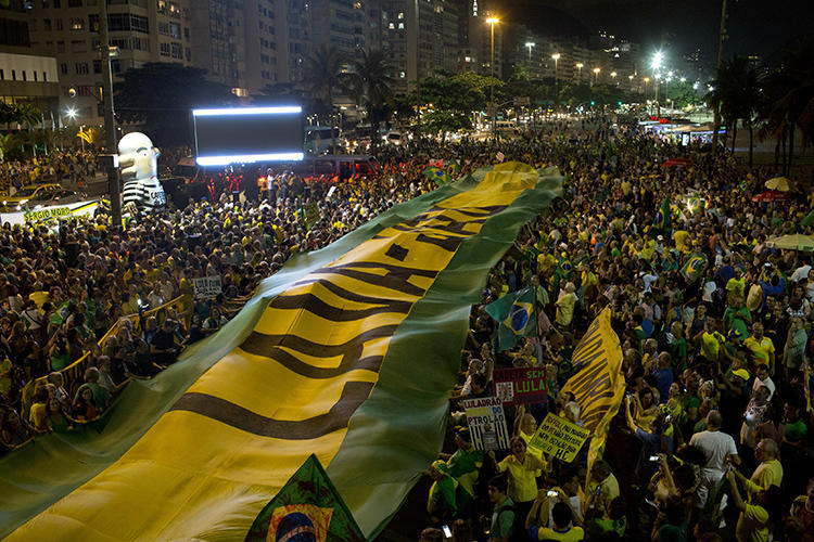 Demonstrators extend a banner in the colors of Brazil's flag during a protest against Brazil's former President Luiz Inacio Lula da Silva in Rio de Janeiro, Brazil, on April 3, 2018. A Brazilian court ordered online magazine Crusoé to remove an article about a judge on April 15, 2019. (AP Photo/Silvia Izquierdo)