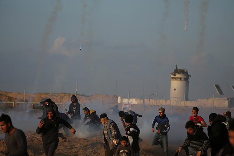 Demonstrators run as Israeli troops fire tear gas canisters in the southern Gaza Strip on April 19, 2019. At least four Palestinian journalists were injured by Israeli troops during the protests. (Reuters/Ibraheem Abu Mustafa)