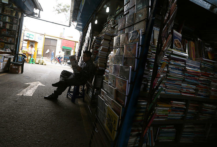 A man reads a newspaper at a market in Lima, in September 2018. A Peru court has ordered assets for Ojo Público and two journalists to be frozen. (Reuters/Mariana Bazo)