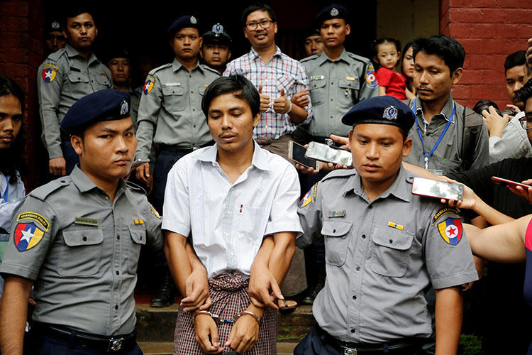 Police escort Reuters journalist Kyaw Soe Oo and Wa Lone from a court hearing in Yangon in August 2018. The Myanmar Supreme Court has upheld their seven-year conviction. (Reuters/Ann Wang)