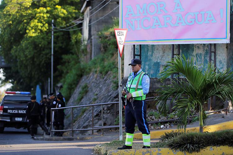 Un funcionario policial mantiene guardia en las oficinas de 100% Noticias en Managua, Nicaragua el 22 de diciembre de 2018. El juicio de los periodistas Lucía Pineda y Miguel Mora fue recientemente suspendido sin fijarse nueva fecha. (Reuters/Oswaldo Rivas)