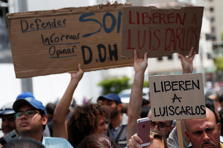 """People hold placards reading """"Free Luis Carlos"""" outside the office of Venezuela's attorney general in Caracas on March 12, 2019. The journalist was released later on March 12. (Reuters/Carlos Garcia Rawlins)"""