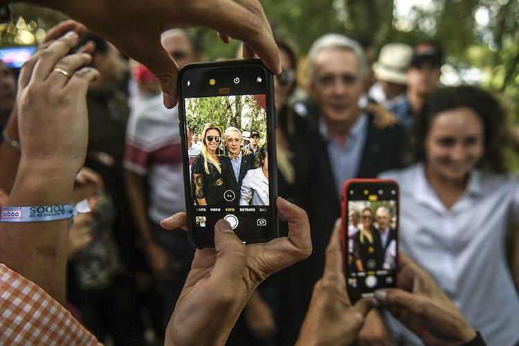 Álvaro Uribe, al centro, posa para fotografías con sus partidarios en su casa, en Rionegro, Colombia, en junio de 2018. El expresidente colombiano presentó una demanda civil por difamación en Estados Unidos contra el periodista Daniel Coronell. (AFP/Joaquín Sarmiento)