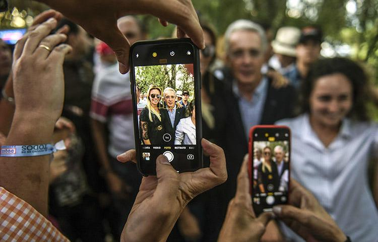 Álvaro Uribe, center, poses for pictures with supporters at his home in Rionegro, Colombia, in June 2018. Colombia's former president filed a civil defamation suit in the U.S. against journalist Daniel Coronell. (AFP/Joaquin Sarmiento)